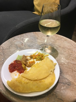 A glass of wine and dholl puri at the Air Mauritius Business Class Lounge in Mauritius
