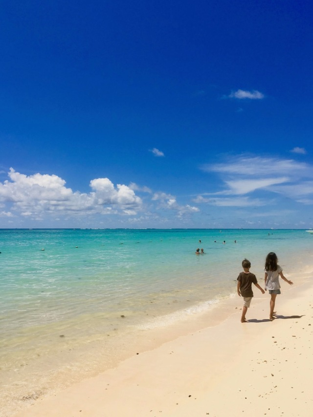 Kids walking on Trou aux Biches Beach: one of the best beach for swimming in Mauritius