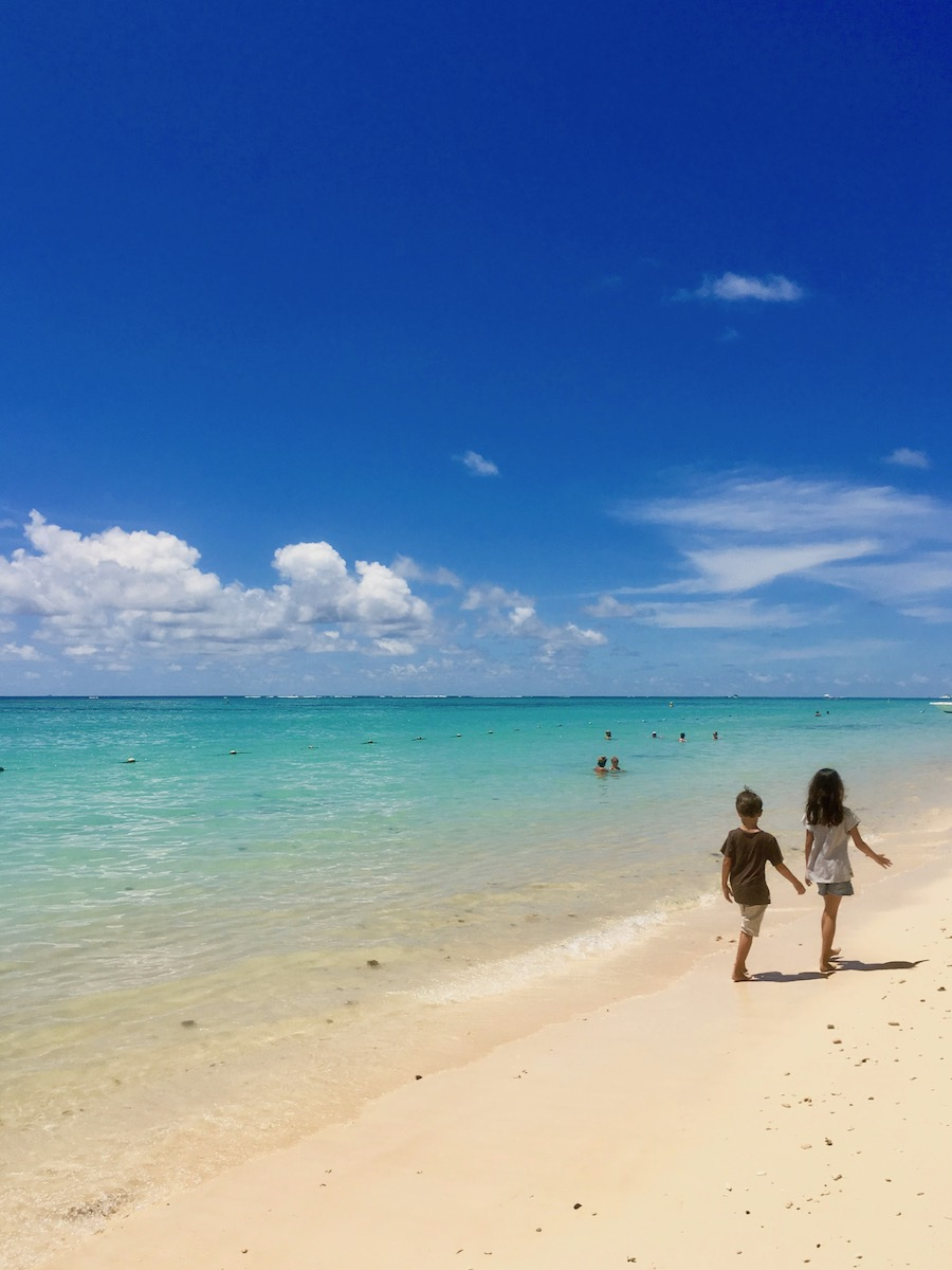 Kids walking on Trou aux Biches Beach: one of the best beaches for Swimming in Mauritius